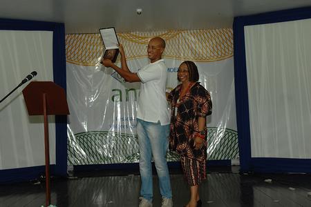 Representando Dona Ivone Lara, o neto André Luiz Lara exibe a placa comemorativa ao Dia Internacional da Mulher